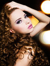 Beautiful young woman with long curly hairs portrait of a over bright night lights Royalty Free Stock Photo