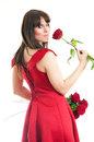 Beautiful young woman long red dress standing white background holding red rose Royalty Free Stock Image