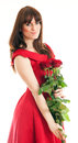 Beautiful young woman long red dress standing white background holding red rose Stock Photo