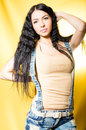 Beautiful young woman looking at camera wearing jeans shorts sexy girl on yellow background Stock Photos