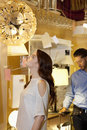 Beautiful young woman looking at lighting fixture hanging while man browsing in background Stock Photos