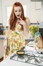Beautiful young woman looking at omelet in frying pan Royalty Free Stock Photography