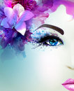 Beautiful young woman looks straight. Light blooming orchid decorated abstract hair. Royalty Free Stock Photo