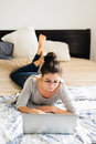 Beautiful young woman lying on bed, working. Home office. Royalty Free Stock Photo