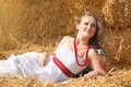 Beautiful young woman lying on a haystack in bright sunny day Royalty Free Stock Photography