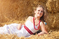 Beautiful young woman lying on a haystack in bright sunny day Royalty Free Stock Images