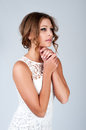 Beautiful young woman with makeup in white dress posing on grey background her hands folded the chest Royalty Free Stock Photo