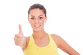Beautiful young woman making thumbs up sign showing Royalty Free Stock Photography