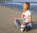 Beautiful young woman meditating on the beach Royalty Free Stock Photography