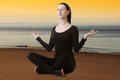 Beautiful young woman meditating on the beach seaside background Stock Photo