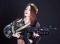 Beautiful young woman in a military uniform with an assault rifl rifle over black background Stock Photos