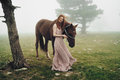 Beautiful young woman in the mountains walking with her horse Royalty Free Stock Photo