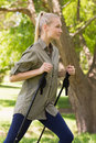 Beautiful young woman nordic walking in park side view of a the Stock Photos