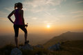Beautiful young woman observing sunset after running on a mountian with bottle of water in hand Stock Photo
