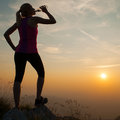 Beautiful young woman observing sunset after running on a mountian with bottle of water in hand Royalty Free Stock Image