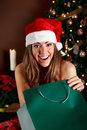 Beautiful young woman opening a christmas gift in front of tree Royalty Free Stock Photos