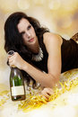 Beautiful young woman partying with champagne in a glamorous evening outfit lying on the floor amongst gold party streamers a Stock Image