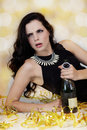 Beautiful young woman partying with champagne in a glamorous evening outfit lying on the floor amongst gold party streamers a Royalty Free Stock Image