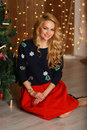 Beautiful young woman with perfect makeup and stylish hair sitting on the floor near Christmas tree Royalty Free Stock Photo