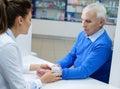 Beautiful young woman pharmacist measuring blood pressure to senior man customer in pharmacy.
