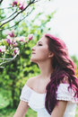 Beautiful young woman with pink hair in the park in white dress Royalty Free Stock Photo