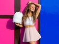 Beautiful young woman in a pink skirt posing near wall with bright cotton candy summer warm evening Royalty Free Stock Photo