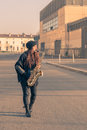 Beautiful young woman playing tenor saxophone in the city streets Stock Images