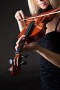 Beautiful young woman playing violin over black background Royalty Free Stock Photography