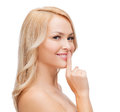 Beautiful young woman pointing finger to lips Stock Photos
