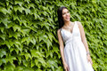 Beautiful young woman posing with green leaves in the background Royalty Free Stock Photo