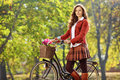 Beautiful young woman posing in a park with a bike her Stock Photo