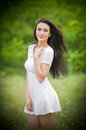 Beautiful young woman posing in a summer meadow. Portrait of attractive brunette girl with long hair relaxing in nature, outdoor Royalty Free Stock Photo