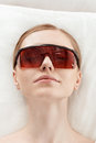 Beautiful young woman in protective glasses take laser skin care