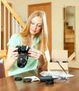 Beautiful young woman reading manual for camera at home behind table Stock Photos