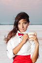 Beautiful young woman with red bow tie portrait of holding cup outdoor Stock Image