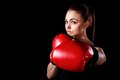 Beautiful young woman in red boxing gloves over black background Royalty Free Stock Photography