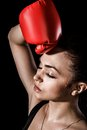 Beautiful young woman in a red boxing gloves over black background Stock Photos