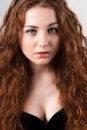 Beautiful young woman with red hairs portrait of in black dress standing on grey background full length Stock Photos