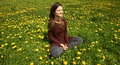 Beautiful young woman relaxing on a meadow with many dandelions in the spring sun. Smiling with copyspace. Royalty Free Stock Photo