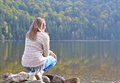 Beautiful young woman relaxing near a lake on in autumn landscape Royalty Free Stock Image