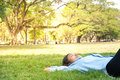 Beautiful young woman relaxing at the park,in green grass meadow Royalty Free Stock Photo