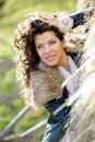 Beautiful young woman relaxing under a hay stack in autumn Royalty Free Stock Photography