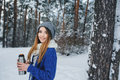 Beautiful young woman relaxing on winter walk in snowy forest, candid capture Royalty Free Stock Photo