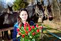 Beautiful young woman with roses and black horses standing bunch of before Royalty Free Stock Image
