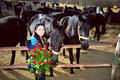 Beautiful young woman with roses and black horses standing bunch of before Royalty Free Stock Photography