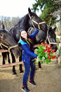 Beautiful young woman with roses and black horses standing bunch of before Royalty Free Stock Images