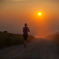 Beautiful young woman runns cross country on a mountian path at sandy sunset Stock Photography