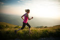 Beautiful young woman runs cross country on a mountian path at sunrise Stock Photo