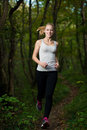 Beautiful young woman runs in forest active runner running Stock Images