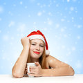 Beautiful young woman in santa claus hat sitting at the table wi with white cup on blue background with snowflakes Stock Photography